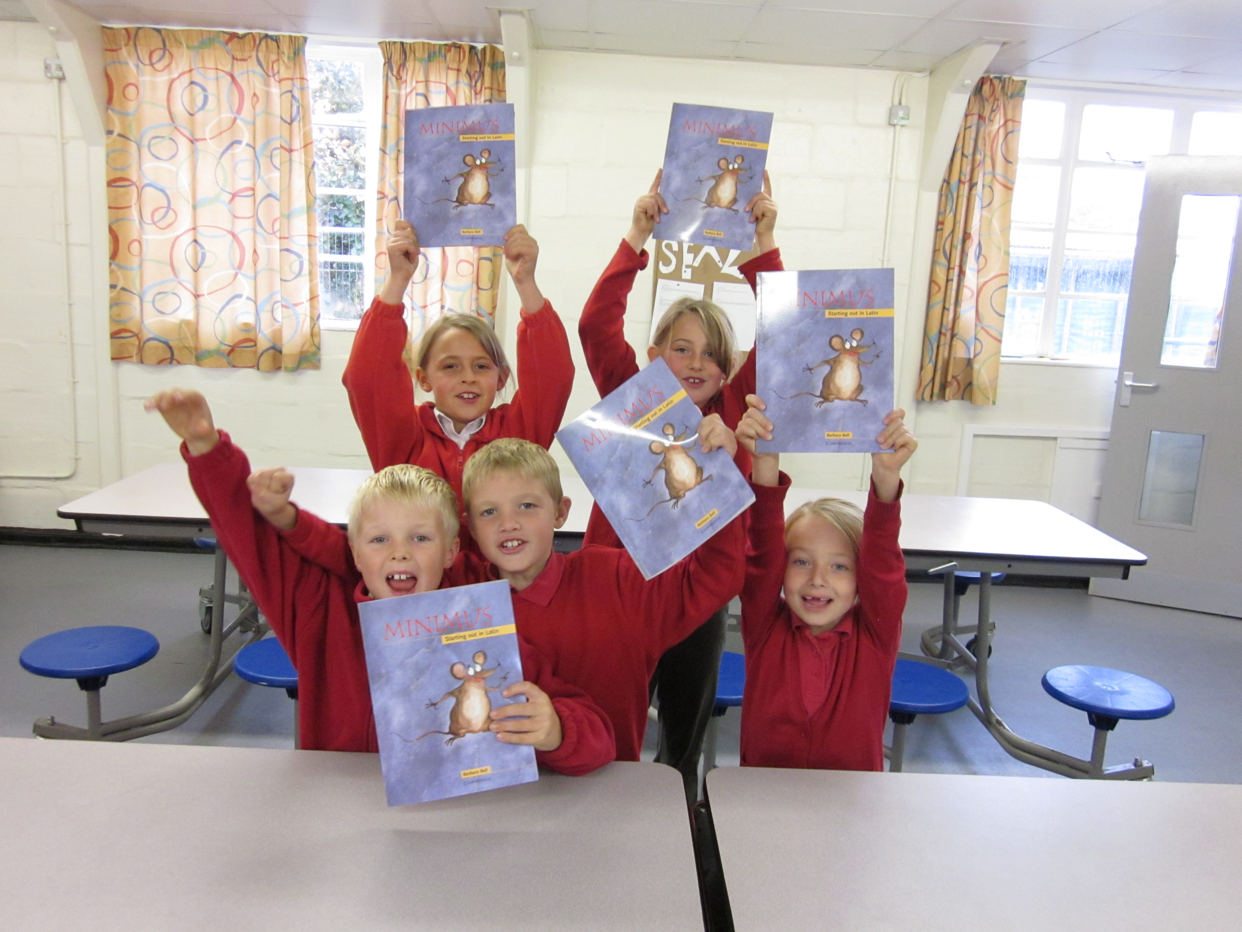 Primary pupils holding Minimus textbooks